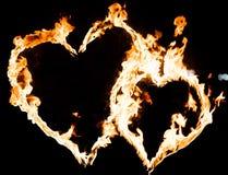 Twee brandende harten tegen een donkere achtergrond dicht omhoog royalty-vrije stock afbeelding