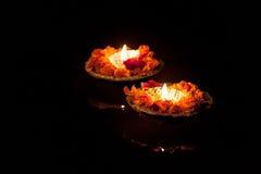 Twee brandende poojakaarsen bij nacht op de rivier Ganges stock afbeelding