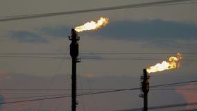Twee brandende toortsen bij de raffinaderij tegen de bewolkte hemel stock video