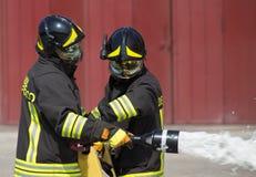 Twee brandweerlieden in actie met schuim Royalty-vrije Stock Fotografie