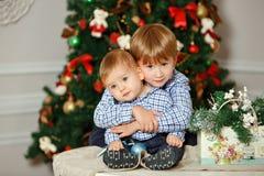 Twee broers in blauw overhemd die en bij Kerstmis glimlachen koesteren stock afbeeldingen
