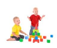 Twee broers bouwt stuk speelgoed de bouw van gekleurde kubussen Stock Foto's