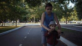 Twee broers die een schopautoped in een de zomerpark berijden stock video