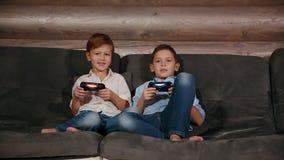Twee broers die op de laag en de zeer emotionele het spelen videospelletjes met draadloze bedieningshendel zitten stock videobeelden