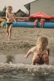 Twee broers die op het strand spelen Stock Foto