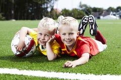 Twee broers die op voetbalgebied liggen Stock Afbeelding