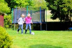 Twee broers die voetbal in de tuin spelen royalty-vrije stock foto's