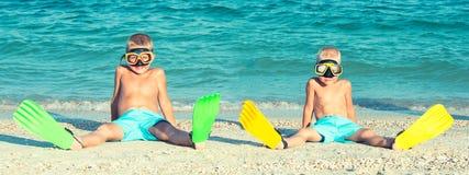 Twee broers in maskers en vinnen zitten op het strand Kleine duikers royalty-vrije stock afbeelding