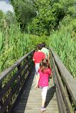 Twee broers met de kleine zuster die onderaan de loopbrug lopen Stock Fotografie