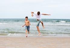 Twee broers van een tiener die op de oceaan, de vriendschap o spelen stock afbeeldingen