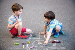 Twee broerssibling jong geitjejongen die pret met het verkeersauto van de beeldtekening hebben met krijt Creatieve vrije tijd voo royalty-vrije stock afbeelding