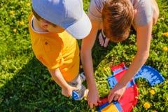 Twee broersspelen met een stuk speelgoed auto op het groene grasgazon royalty-vrije stock fotografie