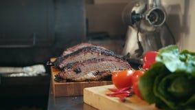 Twee brokken van gerookt borststukvlees op een houten raad stock videobeelden