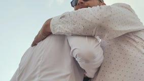 Twee brutale mensen in witte overhemden en een baard begroeten elkaar met een handdruk stock footage