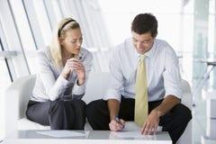 Twee businesspeoplezitting in bureauhal het spreken Stock Afbeelding