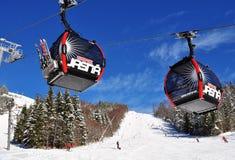 Twee cabines van de kabelbaan en de skiërs op de helling van de berg Royalty-vrije Stock Foto