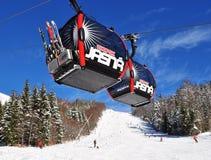 Twee cabines van de kabelbaan en de skiërs op de skihelling van moun Royalty-vrije Stock Afbeeldingen