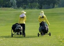 Twee caddies op een golfcursus Stock Foto's