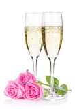 Twee champagneglazen en roze namen bloemen toe Stock Foto