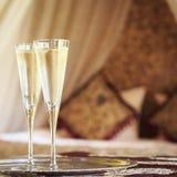 Twee champagneglazen met oosters luifelbed bij de achtergrond royalty-vrije stock foto