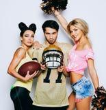 Twee charmante cheerleader meisjes met een bal, pp-Stofdoek en strateeg het Amerikaanse voetbalster stellen met een helm royalty-vrije stock fotografie
