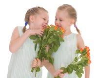 Twee charmante meisjes met boeketten van rozen. Stock Foto's