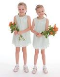 Twee charmante meisjes met boeketten van rozen. Stock Afbeelding