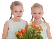 Twee charmante meisjes met boeketten van rozen. Stock Fotografie