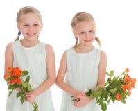 Twee charmante meisjes met boeketten van rozen. Royalty-vrije Stock Afbeeldingen