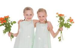 Twee charmante meisjes met boeketten van rozen. Royalty-vrije Stock Foto's