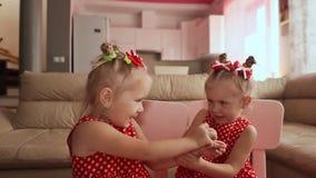 Twee charmante tweelingzusters vertroetelen elkaar, die met hun handen samen spelen stock footage