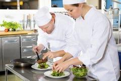 Twee chef-koks bereidt lapje vleesschotel bij gastronomisch restaurant voor royalty-vrije stock afbeeldingen