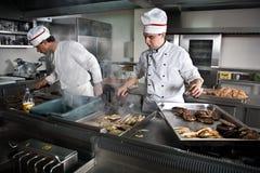 Twee chef-koks op het werk Stock Afbeeldingen