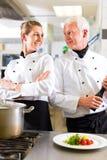 Twee chef-koks in team in hotel of restaurantkeuken royalty-vrije stock afbeeldingen