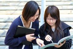 Twee Chinese universitaire studenten op campus Royalty-vrije Stock Afbeeldingen