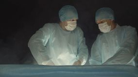Twee chirurg artsen voeren een handeling gebruikend een moderne methode en een behandeling met vloeibare stikstof uit en cryother stock footage