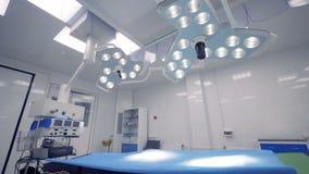 Twee chirurgische lampen die boven het bed in een werkende ruimte hangen Heldere chirurgieruimte met modern materiaal stock videobeelden