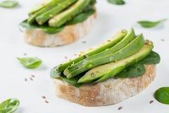 Twee ciabattatoost met gesneden avocadoolijfolie, spinazie en vlas en sesamzaden Gezond vegetarisch Ontbijt  stock fotografie