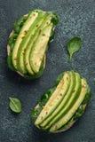 Twee ciabattatoost met gesneden avocadoolijfolie, spinazie en vlas en sesamzaden Gezond vegetarisch Ontbijt op a stock afbeeldingen