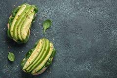 Twee ciabattatoost met gesneden avocadoolijfolie, spinazie en vlas en sesamzaden Gezond vegetarisch Ontbijt op a royalty-vrije stock foto's