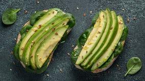 Twee ciabattatoost met gesneden avocadoolijfolie, spinazie en vlas en sesamzaden Gezond vegetarisch Ontbijt op dark stock foto