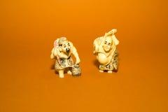 Twee cijfers van Chinese mensen op een oranje achtergrond Stock Foto