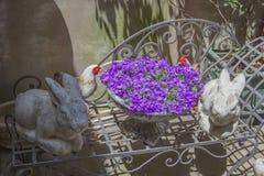 Twee cijfers van een tuinkonijn bevinden zich met een boeket van lavendelbloemen op een metaalbank Stock Fotografie