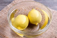 Twee citroenen in een kom water Stock Fotografie