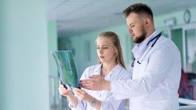 Twee collega's arts die en het middelgrote schot van de Röntgenstraalmomentopname bespreken bekijken stock footage