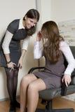 Twee collega's bespreken roddel. De mensen van het bureau Stock Foto