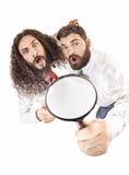 Twee collega's die een vergrootglas met behulp van stock foto