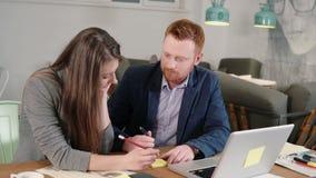 Twee collega's nemen nota's besprekend nieuwe ideeën Creatieve commerciële kleine teamvergadering in modern informeel startbureau stock video