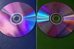 Twee compact-discs op een blauwgroene oppervlakte stock fotografie