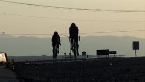 Twee concurrerende fietsers naderen de camera bij de dageraad stock footage